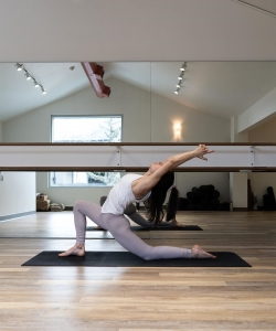 Woman on yoga mat does lunge type yoga pose